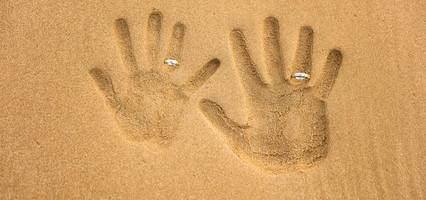 Hand Inprints in Sand Wearing Eternity Rings