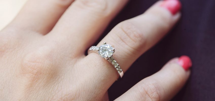Woman's hand wearing a white gold engagement ring