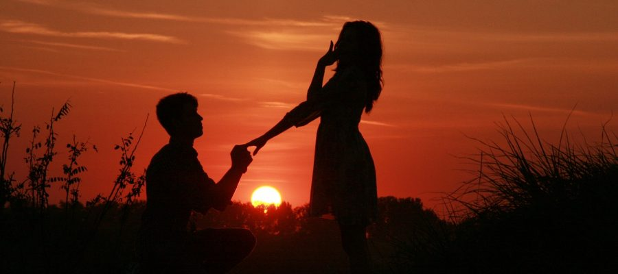 A man proposing to a surprised woman in the sunset