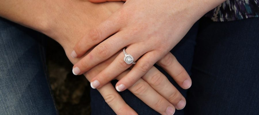 Holding hands with engagement ring on