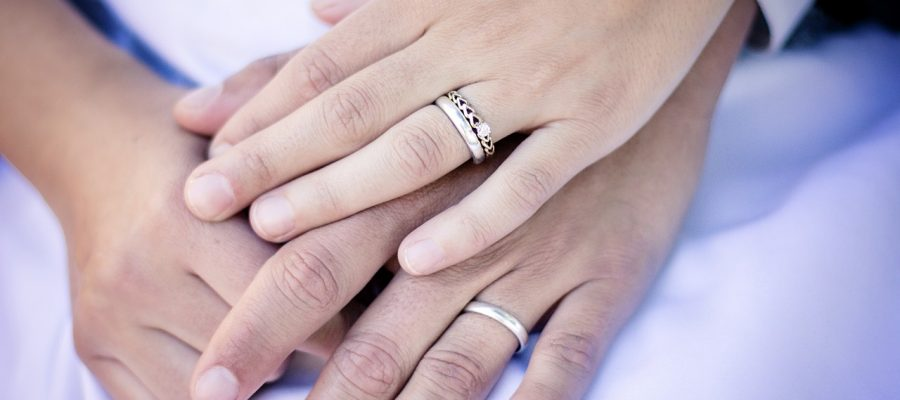 A couple with matching wedding and engagement rings