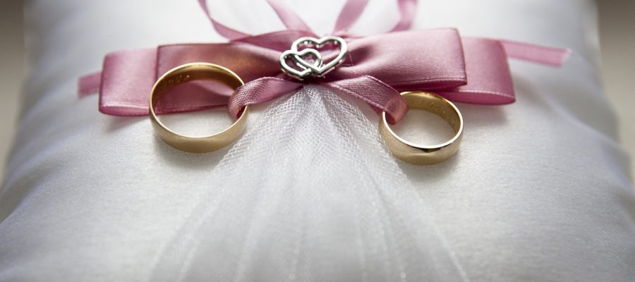 Wedding rings on top of a pink cushion