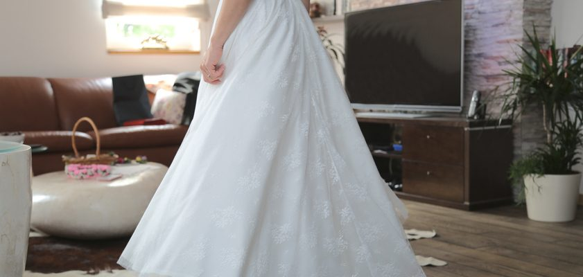 Woman in wedding dress next to TV