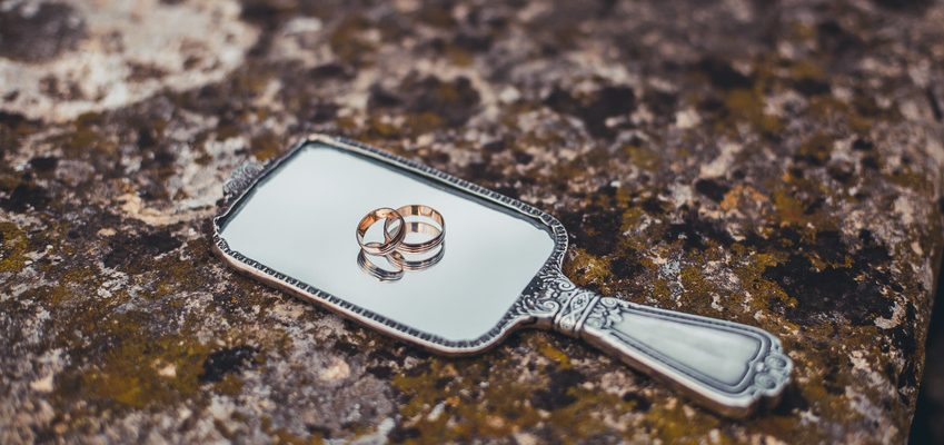 Two old engagement rings on a mirror