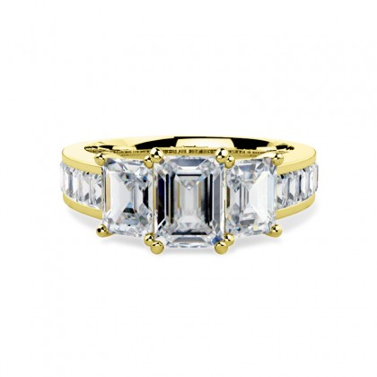 A breathtaking emerald cut three stone diamond ring with shoulders stones in 18ct yellow gold