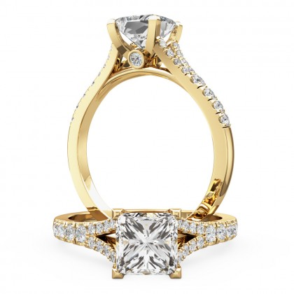 An exquisite princess cut diamond ring with shoulder stones in 18ct yellow gold
