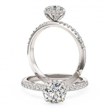 A stylish round brilliant cut diamond halo ring with shoulder stones in 18ct white gold
