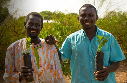 Two farmers holding tree seedlings