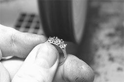 A hand holding a diamond ring
